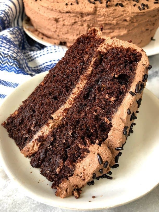 slice of paleo chocolate cake with vegan chcoolate frosting on a plate