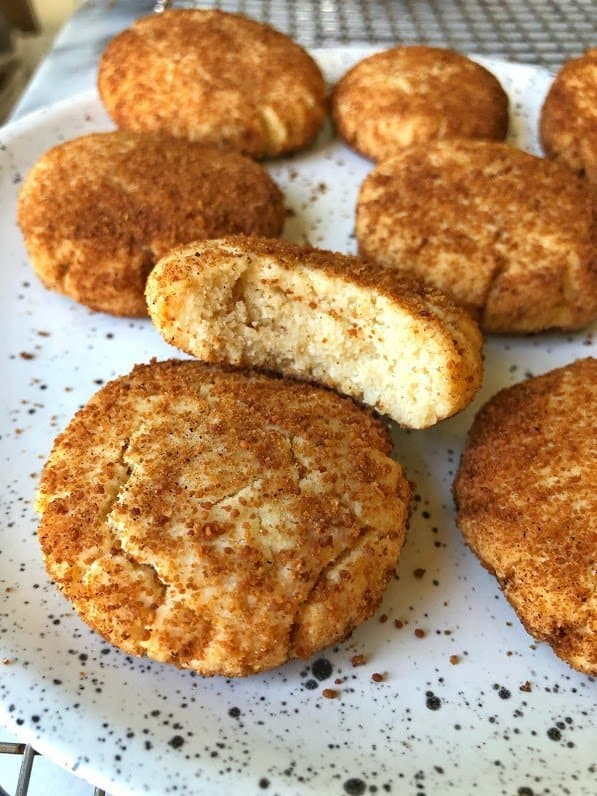 paleo snickerdoodle cookies on a plate with bite taken out of one