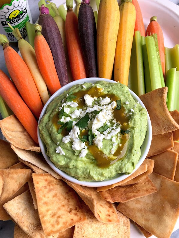 easy avocado feta dip on a tray with carrots and pita chips