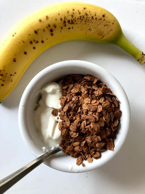 banana with yogurt and granola in a bowl