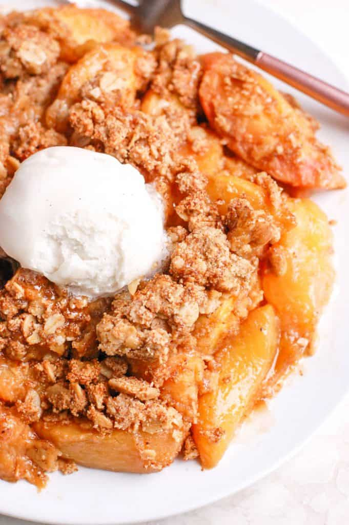 peach crisp on plate with ice cream