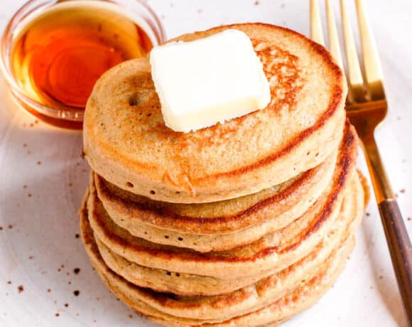 stack of oatmeal pancakes with butter and fork