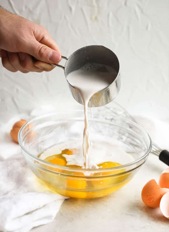 pouring milk into bowl of eggs