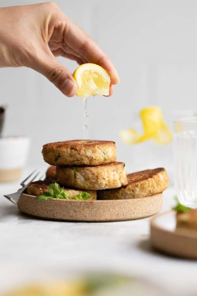 squeezing lemon on tuna patties