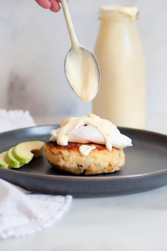 dripping hollandaise on crab cakes eggs benedict