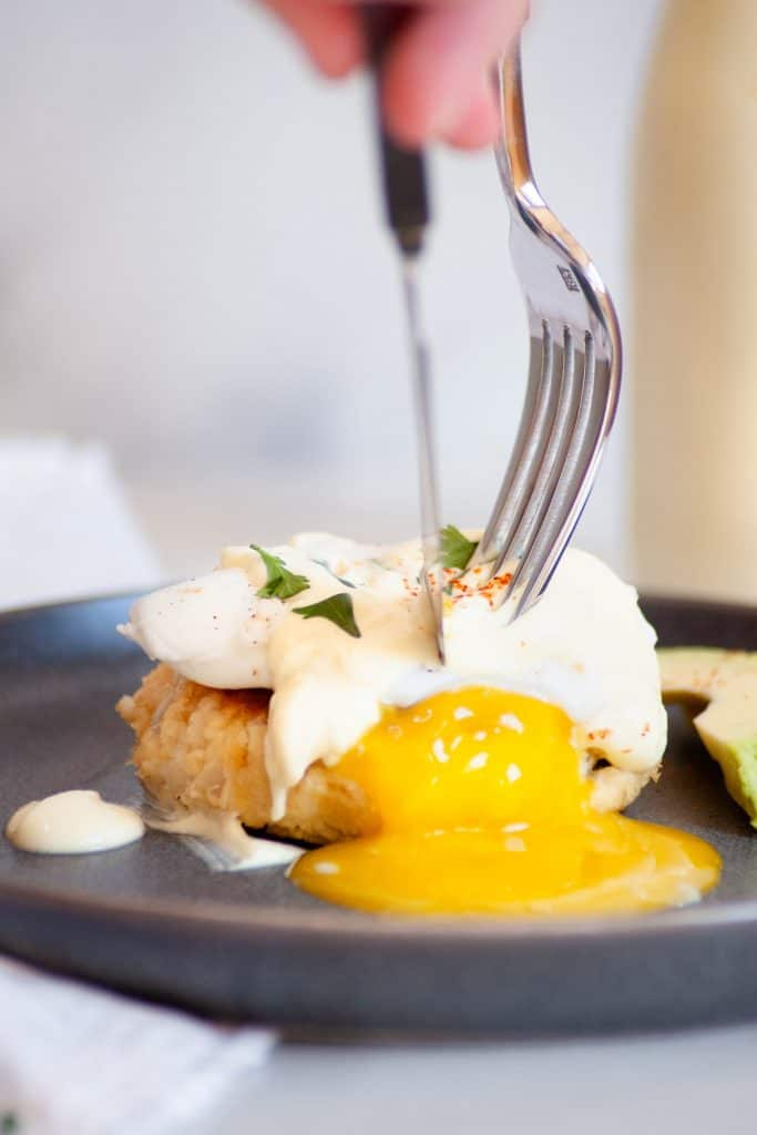 crab cakes eggs benedict yolk popping cutting into it with a knife