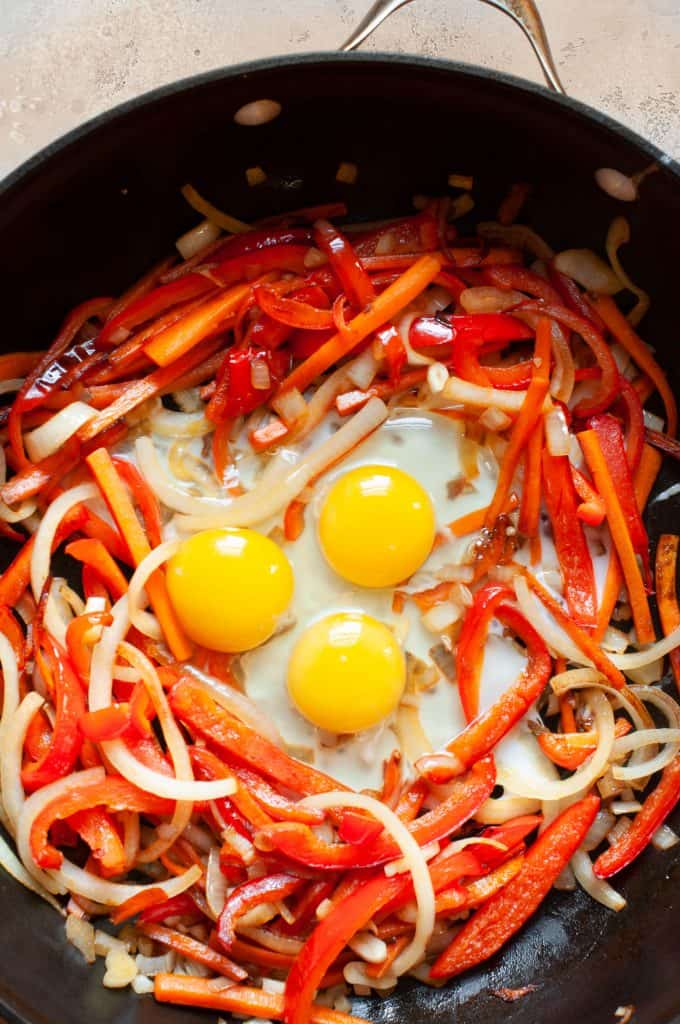 eggs in skillet with peppers and onions