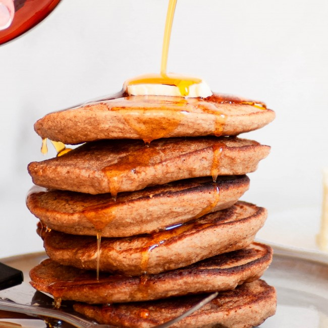 pouring syrup on stack of oatmeal blender pancakes