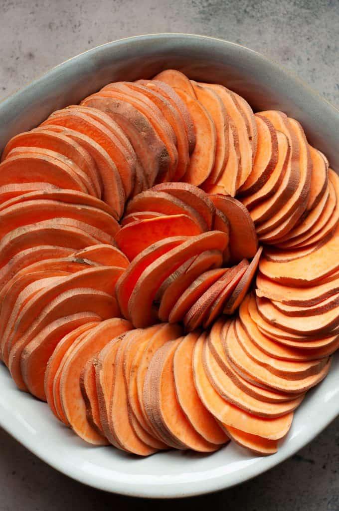 raw sliced sweet potatoes in dish