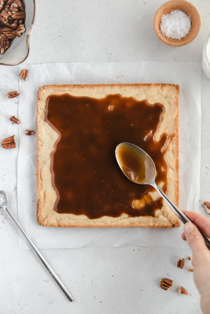 spreading caramel on shortbread