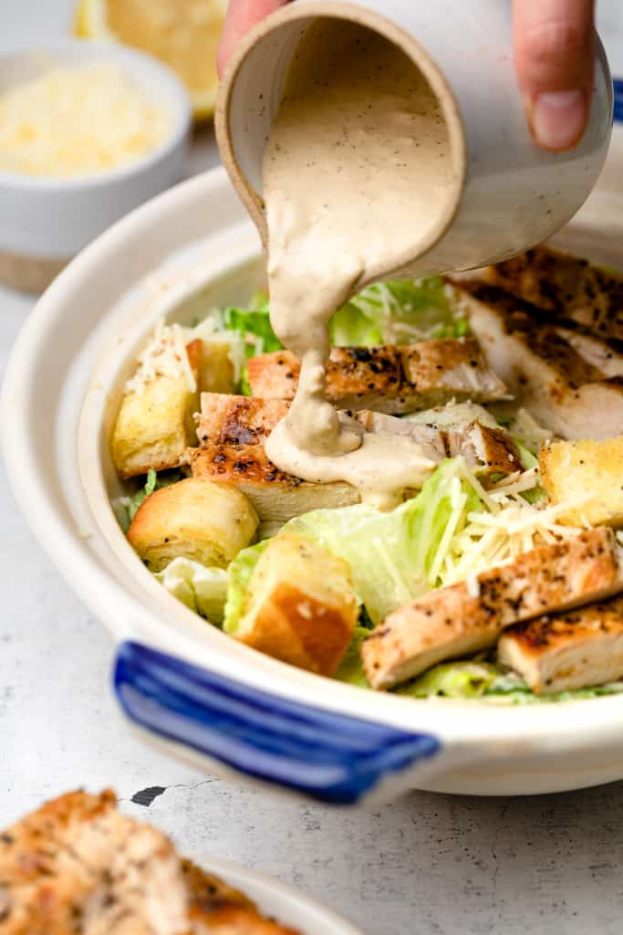 pouring dressing on chicken caesar salad