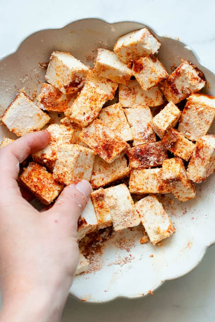 tossing tofu with seasonings
