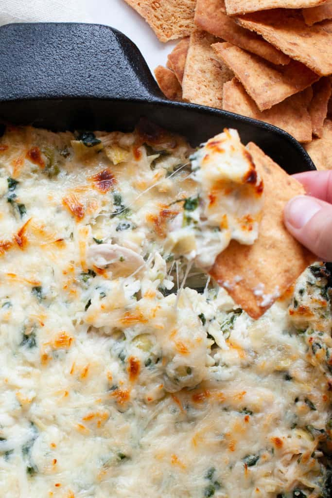 dipping into spinach artichoke dip
