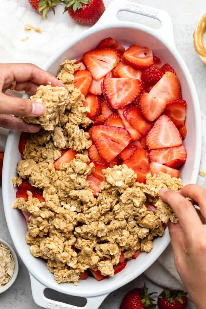 sprinkling crumble onto strawberries